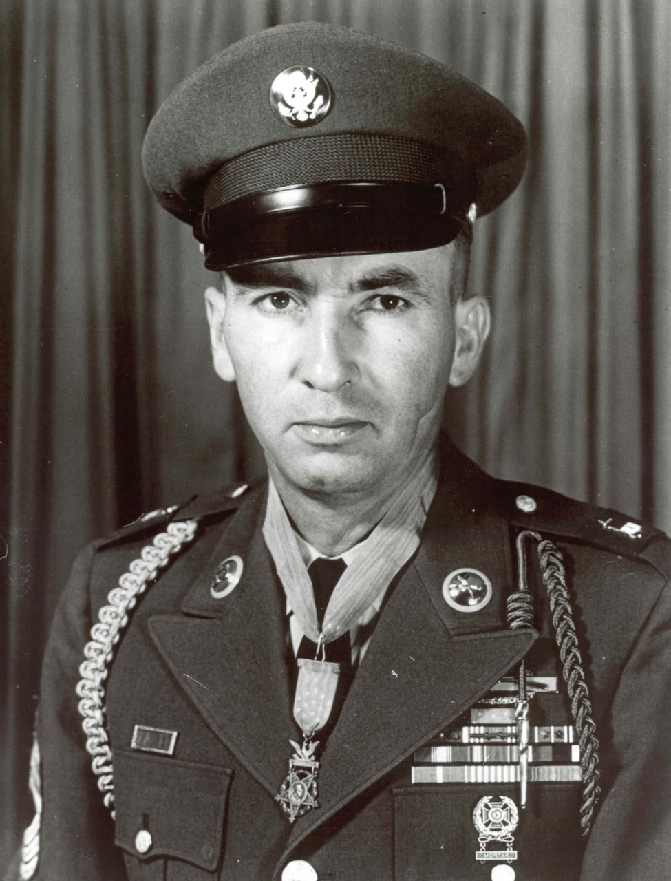 A soldier in his dress uniform and cap wears a Medal of Honor around his neck.