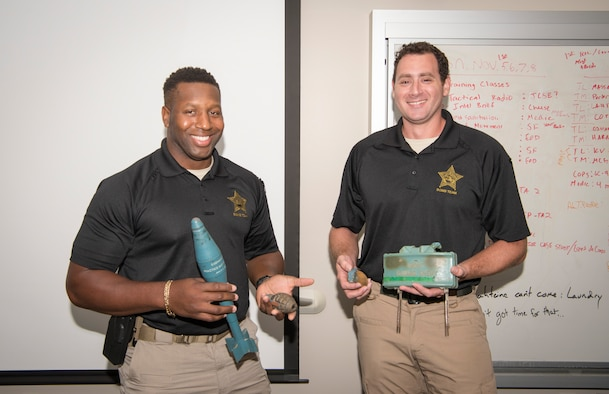 Deputy Bjar Atkins, left, and Deputy Joseph Saponara, right, both Hillsborough County Sheriff's Office bomb technicians, hold up various types of inert military ordnance at MacDill Air Force Base, Fla., Aug. 14, 2019.