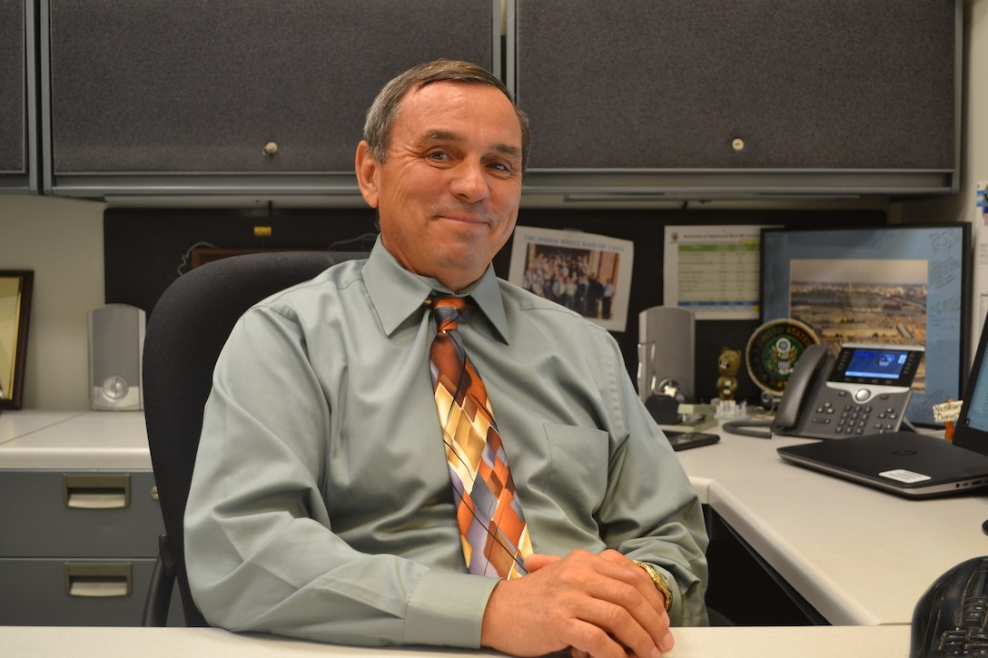 DLA NESO Senior Operations Research Analyst Mark Melius sits at his desk.
