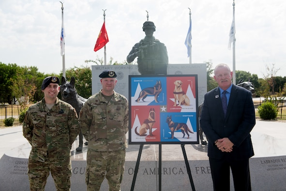 U.S. Air Force Master Sgt. Steven Kaun (left), USAF Military Working Dog program manager, Maj. Matthew Kowalski, 341st Training Squadron commander, and Robert Carr, Post Master of San Antonio, pose for a photo during the Military Working Dog Stamp ceremony Aug. 15, 2019, at Joint Base San Antonio-Medina Annex, Texas.