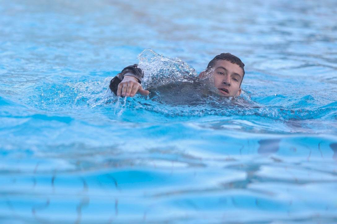A soldier swims in a pool.