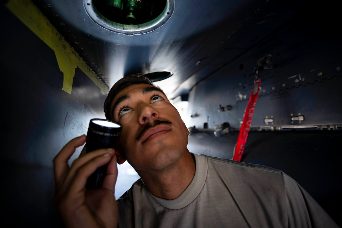 An airman uses a flashlight to look into an aircraft's compartment.