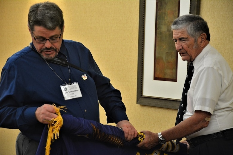 John Clyburn (right), secretary of the 94th Infantry Division Historical Society, holds the 94th's colors as Jim Eisenmann carefully furls and cases them at the society's reunion banquet.  World War II veterans, their families, and current members of the 94th Training Division-Force Sustainment came together to celebrate the 70th anniversary of the 94th IDHS at their annual reunion held in Columbus, Georgia, June 14-15, 2019.