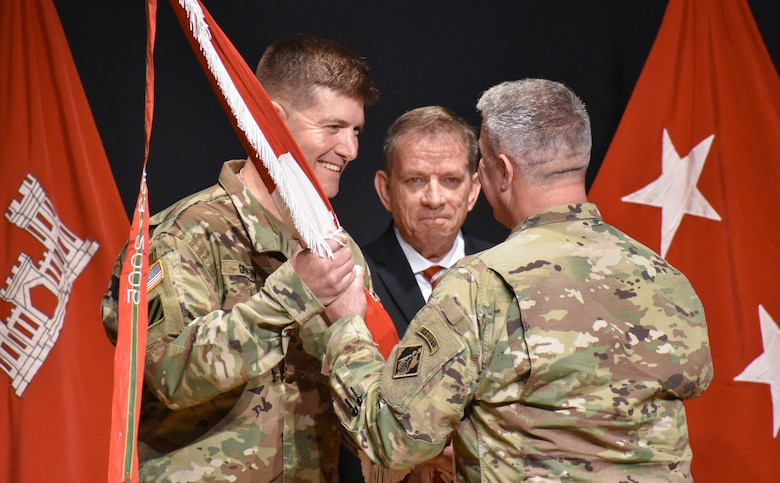 """Maj. Gen. Richard Kaiser, right, deputy chief of engineers and deputy commanding general of the U.S. Army Corps of Engineers, presents the Huntsville Center's guidon to Col. Marvin Griffin, as Albert """"Chip"""" Marin III, Huntsville Center programs director looks on."""