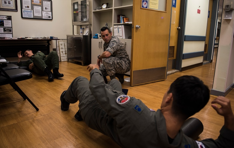 U.S. Air Force Tech. Sgt. David Spade, 8th Medical Operations Squadron physical therapy flight chief, shows pilots from the Republic of Korea Air Force's 111th Fighter Squadron how to use a foam roller during a training session at Kunsan Air Base, Republic of Korea, Aug. 9, 2019. The 8th MDOS physical therapy flight taught the 111th FS pilots how to perform various stretches and exercises to alleviate pain and discomfort they were having. (U.S. Air Force photo by Senior Airman Stefan Alvarez)