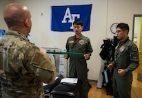 U.S. Air Force Tech. Sgt. Nicholas Ramirez, 8th Medical Operations Squadron physical therapy flight chief, teaches pilots from Republic of Korea Air Force's 111th Fighter Squadron how to stretch their backs, during a training session at Kunsan Air Base, Republic of Korea, Aug. 9, 2019. Pilots often find themselves developing pain in different areas from regularly putting their bodies under high amounts of gravitational forces. (U.S. Air Force photo by Senior Airman Stefan Alvarez)