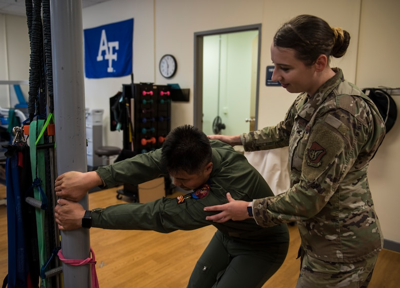 U.S. Air Force Staff Sgt. Michaela Chevalier, 8th Medical Operations Squadron physical therapy technician, teaches a pilot from Republic of Korea Air Force's 111th Fighter Squadron how to stretch his back, during a training session at Kunsan Air Base, Republic of Korea, Aug. 9, 2019. Pilots often suffer from neck and back pain from flying for prolonged hours wearing their equipment. (U.S. Air Force photo by Senior Airman Stefan Alvarez)