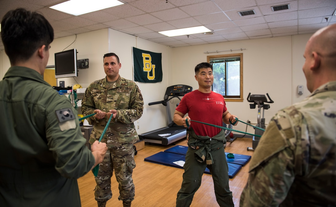 U.S. Air Force Tech. Sgt. Nicholas Ramirez (far right), 8th Medical Operations Squadron physical therapy flight chief, and Master Sgt. Joshua Haney (middle left), 8th Medical Operations Squadron superintendent, teach pilots from Republic of Korea Air Force's 111th Fighter Squadron how to stretch their backs during a training session at Kunsan Air Base, Republic of Korea, Aug. 9, 2019. Pilots often find themselves developing pain in different areas from regularly putting their bodies under high amounts of gravitational forces. (U.S. Air Force photo by Senior Airman Stefan Alvarez)