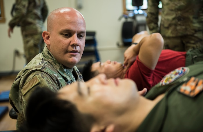 U.S. Air Force Tech. Sgt. Nicholas Ramirez, 8th Medical Operations Squadron physical therapy flight chief, teaches pilots from Republic of Korea Air Force's 111th Fighter Squadron a way to exercise their necks during a training session at Kunsan Air Base, Republic of Korea, Aug. 9, 2019. Pilots often find themselves developing pain in different areas from regularly putting their bodies under high amounts of gravitational forces. (U.S. Air Force photo by Senior Airman Stefan Alvarez)