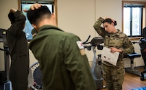 U.S. Air Force Staff Sgt. Michaela Chevalier, 8th Medical Operations Squadron physical therapy technician, teaches pilots from Republic of Korea Air Force's 111th Fighter Squadron how to stretch their necks during a training session at Kunsan Air Base, Republic of Korea, Aug. 9, 2019. Pilots often suffer from neck and back pain from flying for prolonged hours wearing their equipment. (U.S. Air Force photo by Senior Airman Stefan Alvarez)