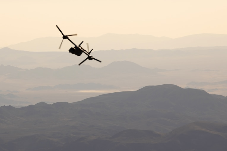 An aircraft flies over mountainous terrain.