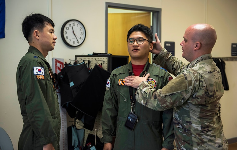 U.S. Air Force Tech. Sgt. Nicholas Ramirez, 8th Medical Operations Squadron physical therapy flight chief, teaches pilots from Republic of Korea Air Force's 111th Fighter Squadron how to adjust their posture during a training session at Kunsan Air Base, Republic of Korea, Aug. 9, 2019. Pilots often suffer from neck and back pain from flying for prolonged hours wearing their equipment. (U.S. Air Force photo by Senior Airman Stefan Alvarez)