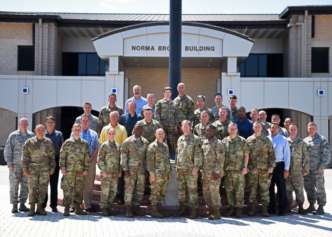 U.S. Air Force personnel from The National Air and Space Intelligence Center pose for a group photo with 17th Training Wing Commander, Col. Andres Nazario, and Command Chief, Chief Master Sgt. Lavor Kirkpatrick, at the Norma Brown Building on Goodfellow Air Force Base, Texas, August 13, 2019. NASIC personnel were shown how the 17th TRW shapes the future of NASIC. (U.S. Air Force photo by Airman 1st Class Ethan Sherwood/Released)