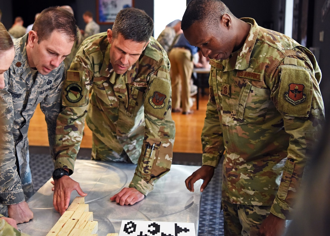 U.S. Air Force Maj. Brandon Stoker and Lt. Col. Tyler Harris from The National Air and Space Intelligence Center, work with Chief Master Sgt. Lavor Kirkpatrick, 17th Training Wing Command Chief, and 17th TRW students to solve puzzles during the mental health fitness challenge at Goodfellow Air Force Base, Texas, August 13, 2019. The challenge included physical and mental exercises to keep individuals both sharp and strong. (U.S. Air Force photo by Airman 1st Class Ethan Sherwood/Released)