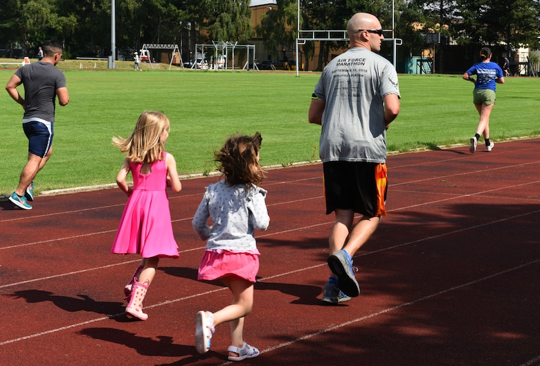 Children follow the lead of Airmen running in the Operation Warm Heart run-a-thon at Royal Air Force Lakenheath, England, Aug. 2, 2019. For each lap completed during the event, the runner's sponsors donated money, which provides emergency funds for Airmen in difficult situations. (Courtesy photo by Carissa Chae)