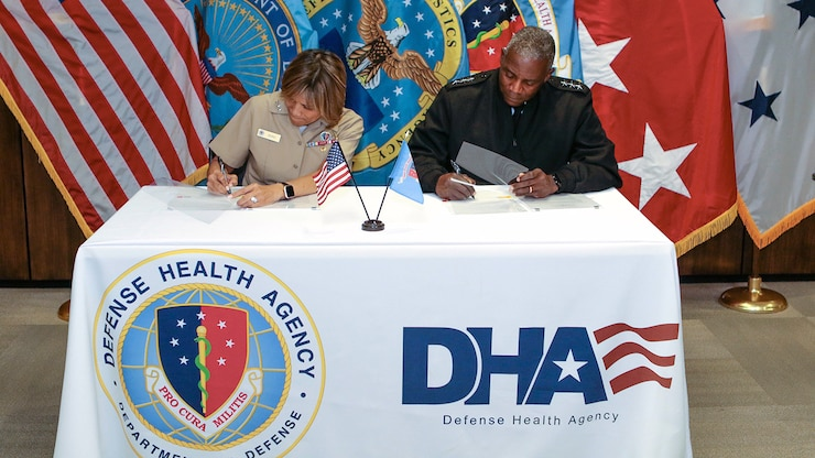 Navy Vice Adm. Raquel Bono, seated left, and Army Lt. Gen. Darrell K. Williams,seated right, sign a memorandum of agreement at a table featuring the DHA emblem