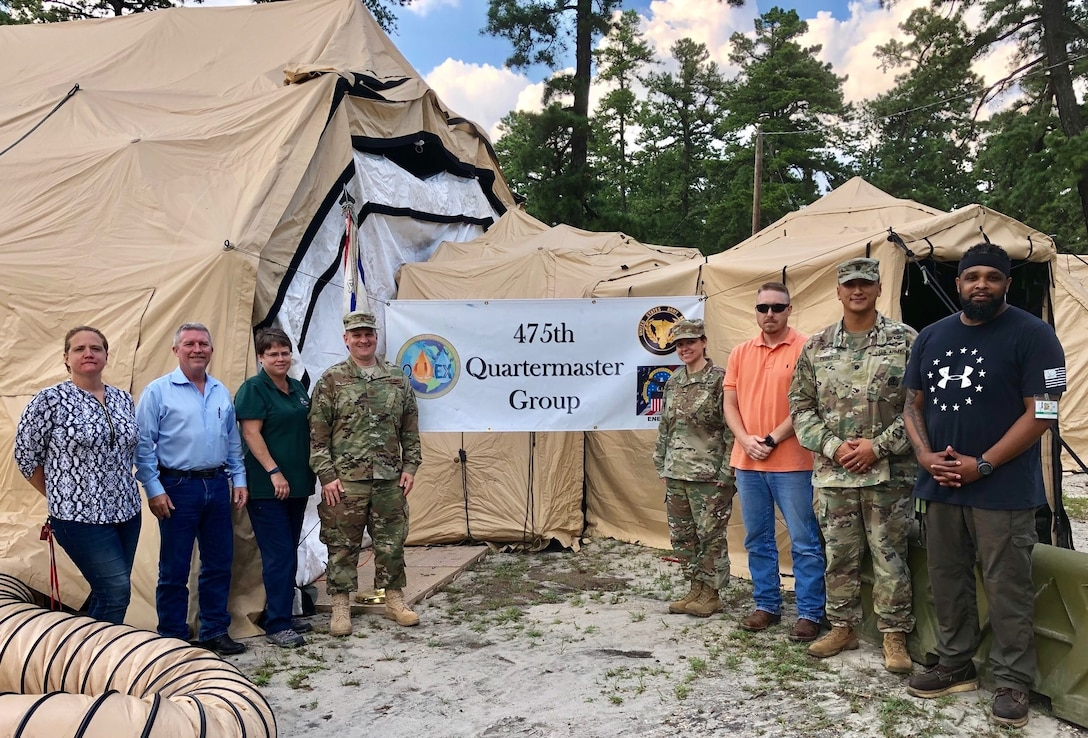 military and civilian personnel stand outside a tent