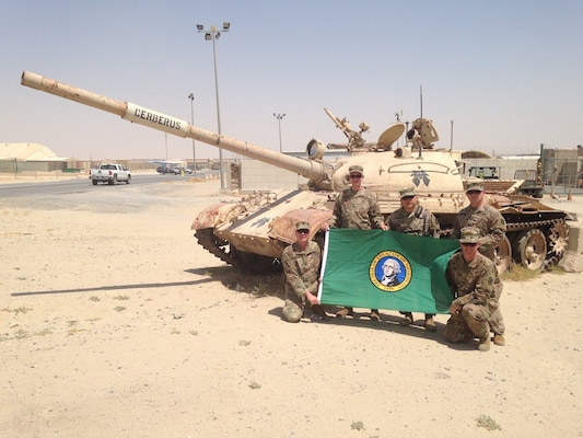 """Members of the 122D Public Affairs Operations Center pose in front of a disabled  tank named """"Cerbrus""""  at Camp Arifjan, Kuwait. Arifjan is known as """"The Gateway"""" because soldiers heading into theater must first check in through Kuwait. From left to right: Master Sgt. Neal Mitchell, Capt. James Deakins, Col. Stanley Seo, Capt. Benjamin Burbank and Maj. Eric Trovillo. (U.S. National Guard photo by Staff Sgt. Michael Tietjen)"""