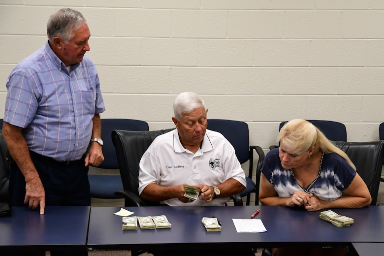 Square and Compass Club members count proceeds from this year's Corn and Sausage Roast fundraiser at Dobbins Air Reserve Base, Ga., Aug. 15, 2019.