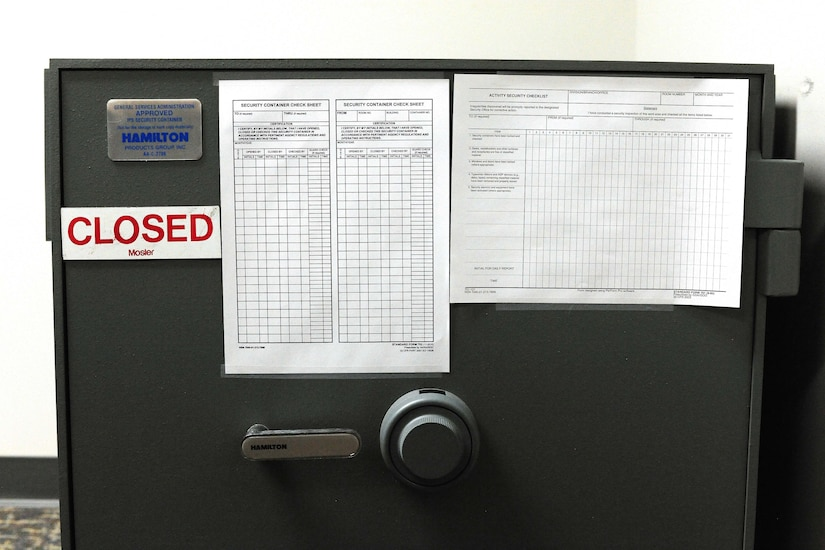 "A safe bears a magnet with the word ""CLOSED.""  Checklists also adorn the safe."
