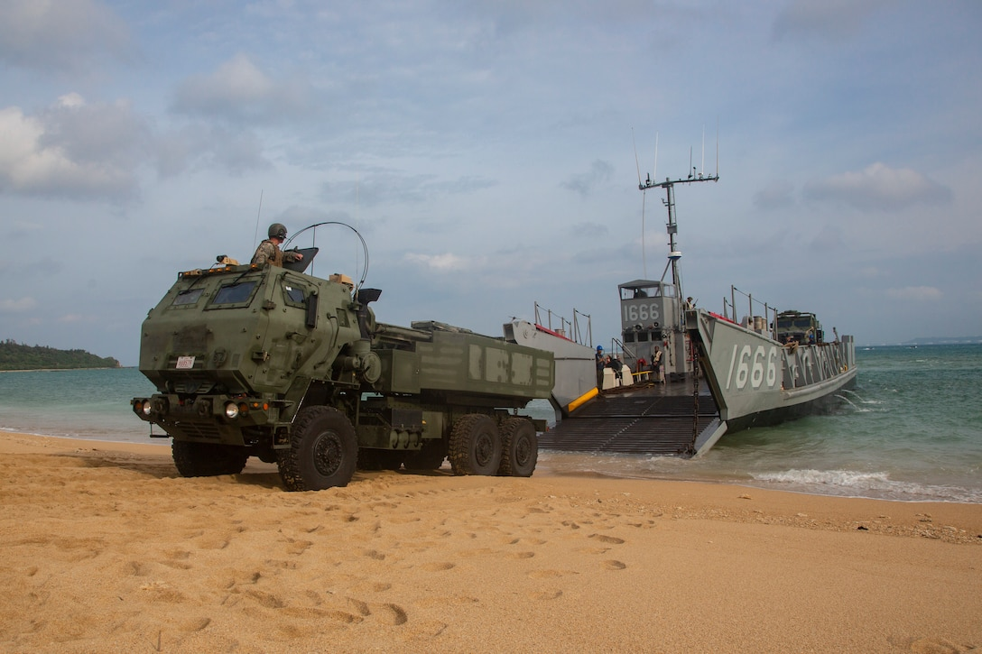 A landing craft, utility assigned to the amphibious transport dock ship USS Green Bay, lowers its ramp to unload a High Mobility Artillery Rocket System from 3rd Battalion, 12th Marine Regiment, 3rd Marine Division, as part of a simulated amphibious raid, at Kin Blue, Okinawa, Japan, Aug. 14, 2019. This simulated amphibious raid marks the first time that HIMARS have been inserted by landing craft, utility, demonstrating the Marine Air-Ground Task Force's ability to conduct combined-arms maneuver from amphibious shipping.