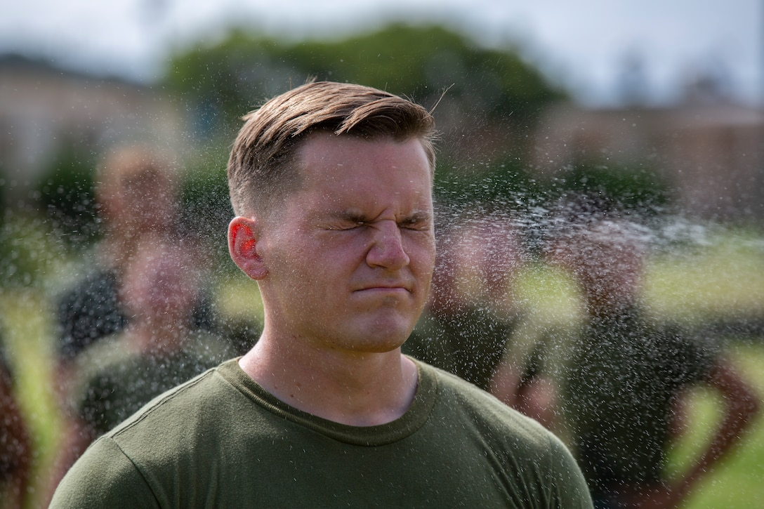 U.S. Marine Cpl. Logan Foster with Headquarters Battalion, 3rd Marine Division, is sprayed with Oleoresin Capsicum Spray during a non-lethal weapons training course on Camp Courtney, Okinawa, Japan, Aug. 16, 2019. The training encompasses classes in the lawful use of force, M1014 Shotgun qualification, and OC Spray qualification. During OC Spray qualification Marines are exposed to OC and conduct a simulated arrest with a non-compliant suspect.