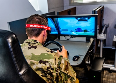 Man sitting at a game console that simulates the effects of impaired driving.