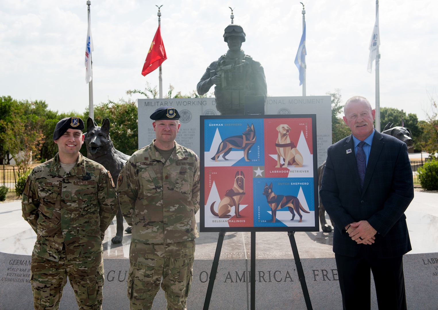 Master Sgt. Steven Kaun (left), USAF Military Working Dog program manager, Maj. Matthew Kowalski, 341st Training Squadron commander, and Robert Carr, Post Master of San Antonio, pose for a photo during the Military Working Dog Stamp ceremony Aug. 15 at Joint Base San Antonio-Medina Annex. The stamp honors dogs who have served in the U.S. armed forces since the U.S. Army created the War Dog Program K-9 Corps and began training man's best friend in March 1942.