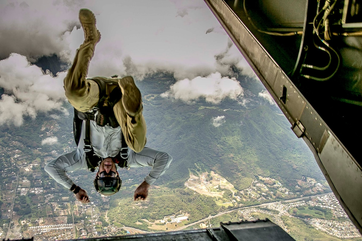 A service member jumps out of an aircraft upside down.