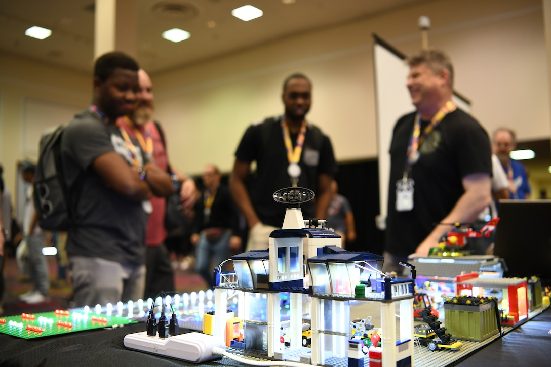 """Attendees visit the 90th Cyberspace Operations Squadron """"Bricks in the Loop"""" display during DEF CON 27 Hacking Conference in Las Vegas, Aug. 9, 2019. """"Bricks in the Loop"""" mimics an Air Force installation to simulate real-world cyber systems in training cyber operators. (U.S. Air Force photo by Tech. Sgt. R.J. Biermann)"""