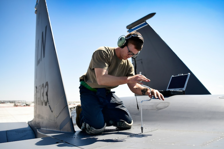 Senior Airman secures a panel on an F-15E Strike Eagle