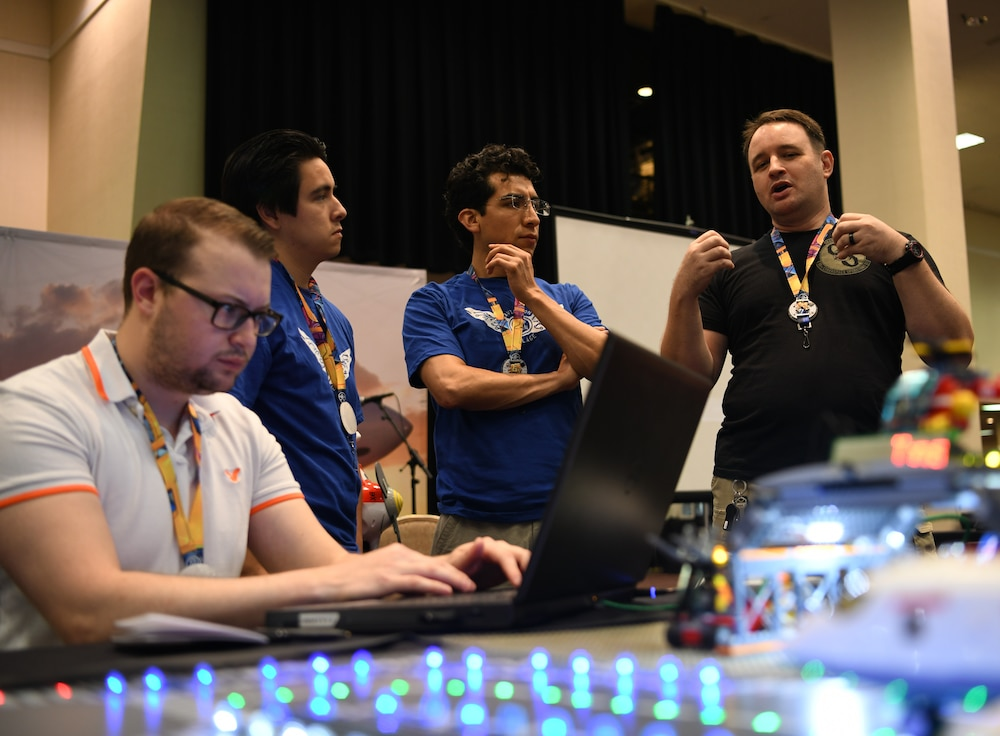 "Cody Jackson (right), 90th Cyberspace Operations Squadron constructive modeler, hosts cyber students for a ""Bricks in the Loop"" presentation at DEF CON 27 Hacking Conference in Las Vegas, Aug. 9, 2019. ""Bricks in the Loop"" mimics an Air Force installation to simulate real-world cyber systems in training cyber operators. (U.S. Air Force photo by Tech. Sgt. R.J. Biermann)"