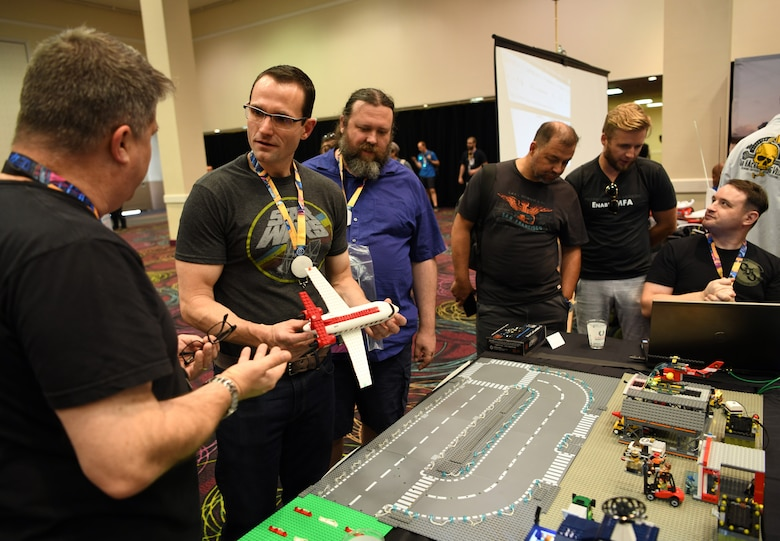 "Scott Thompson, 90th Cyberspace Operations Squadron, systems engineer, hosts Dr. Will Roper, Assistant Secretary of the Air Force for Acquisition, Technology and Logistics, for a ""Bricks in the Loop"" presentation at DEF CON 27 Hacking Conference in Las Vegas, Aug. 9, 2019. ""Bricks in the Loop"" mimics an Air Force installation to simulate real-world cyber systems in training cyber operators. (U.S. Air Force photo by Tech. Sgt. R.J. Biermann)"