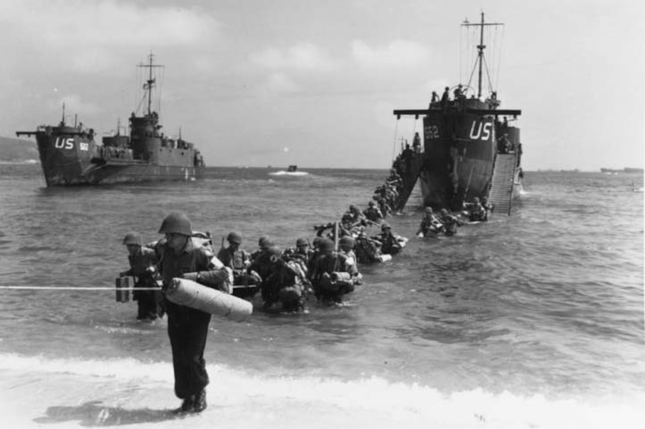 Soldiers wade from ship to beach.
