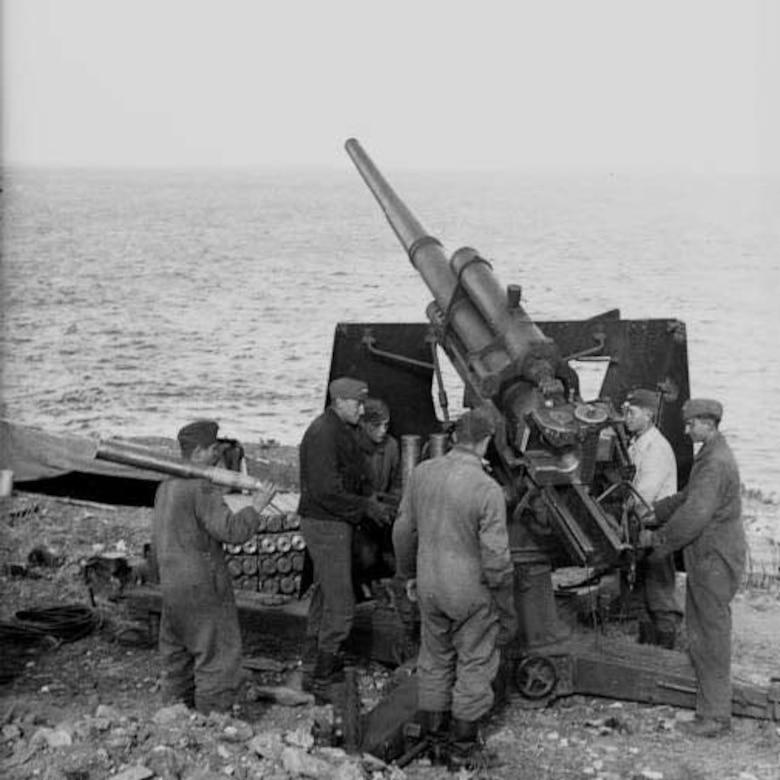 Men stand around howitzer.