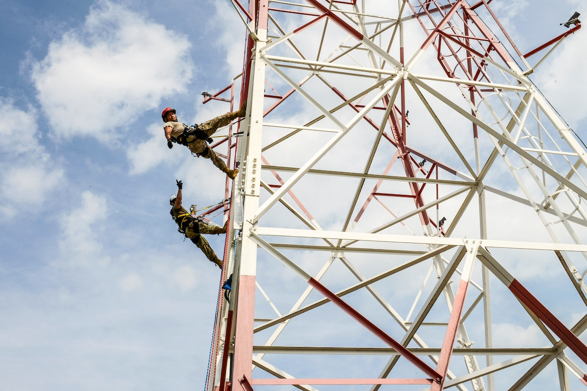 Two airmen climb a metal tower, with blue sky and white clouds in the background.