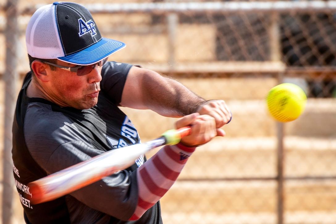A softball player swings a bat at a ball.