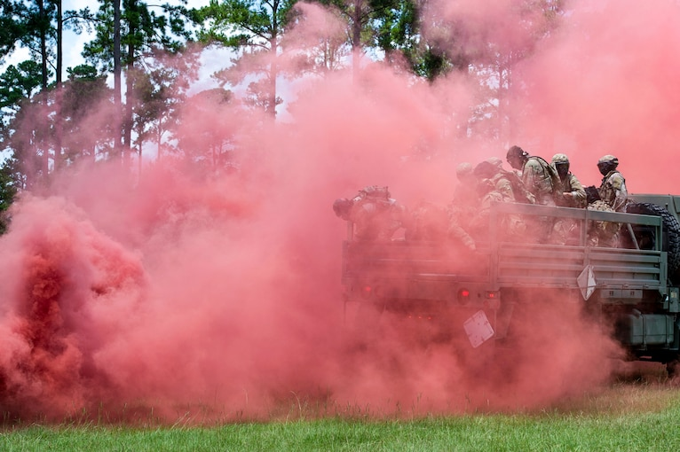 Service members in a vehicle drive on a field through a reddish-pink smoke cloud.