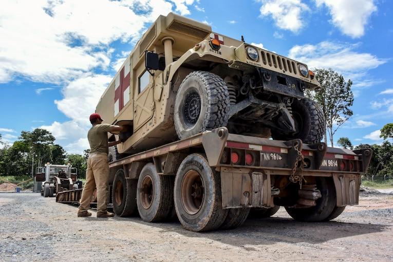 An airman works on a Humvee sitting atop a wheeled platform.