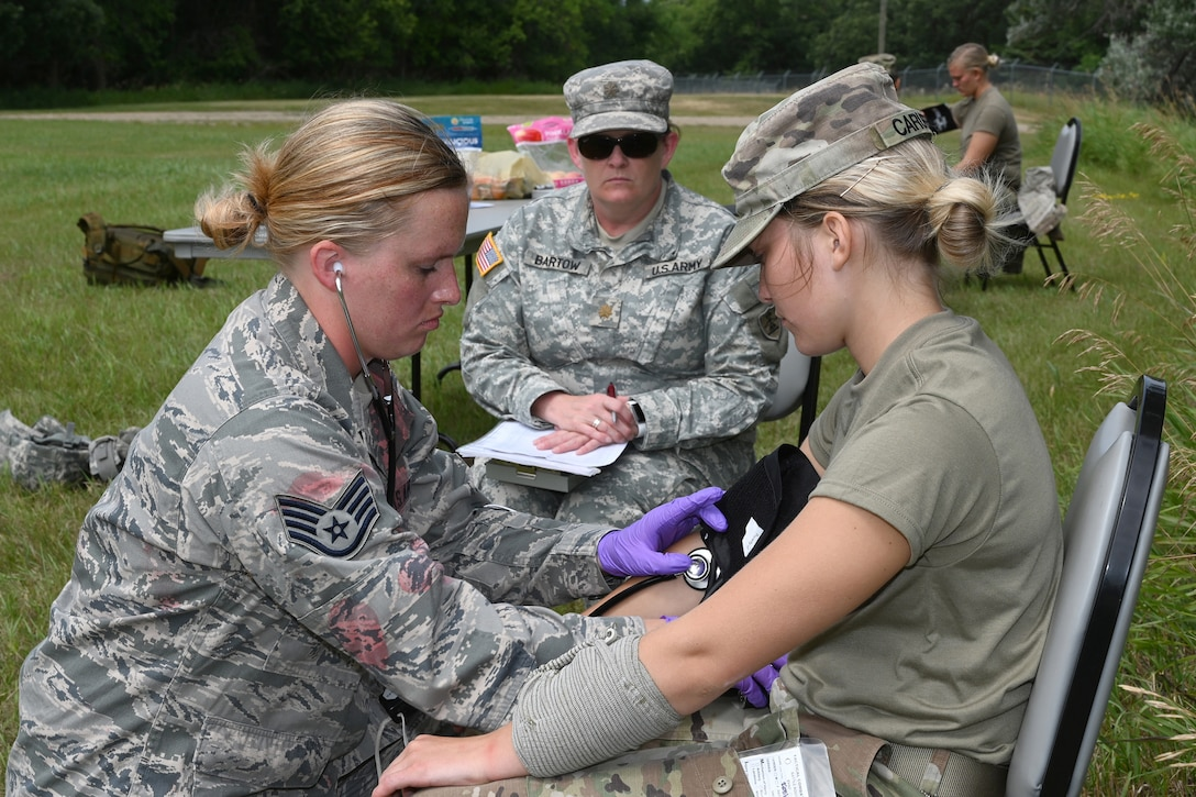 Staff Sgt. Kally Anderson, of the 119th Medical Group, left, applies treatment to Spc. Tallysa Carufel, as Maj. Shelly Bartow observes during Tactical Combat Casualty Care (TCCC) training at Camp Gilbert C. Grafton, N.D., Aug. 9, 2019.