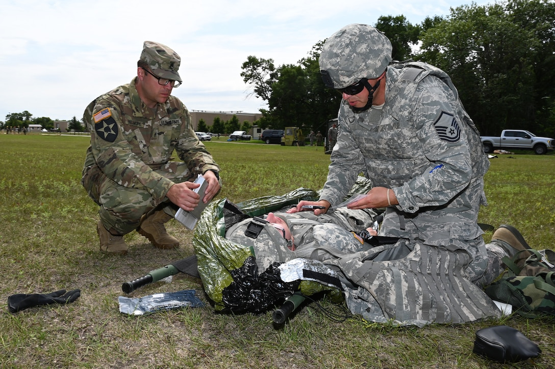 Master Sgt. Nathan Carlson, of the 119th Medical Group, right, applies medical treatment to a simulated injury victim as instructor Staff Sgt. Colton Belmore, of the N.D. Army National Guard, evaluates him during Tactical Combat Casualty Care (TCCC) training at Camp Gilbert C. Grafton, N.D., Aug. 9, 2019.