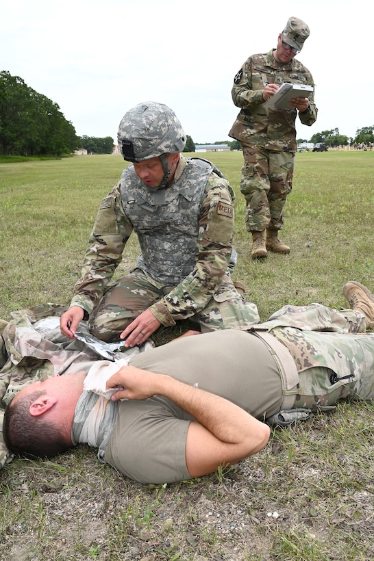 Tech. Sgt. Jeremy Levenhagen, of the 119th Medical Group applies medical treatment to a simulated injury victim as instructor Staff Sgt. Colton Belmore, of the N.D. Army National Guard, evaluates him during Tactical Combat Casualty Care (TCCC) training at Camp Gilbert C. Grafton, N.D., Aug. 9, 2019.