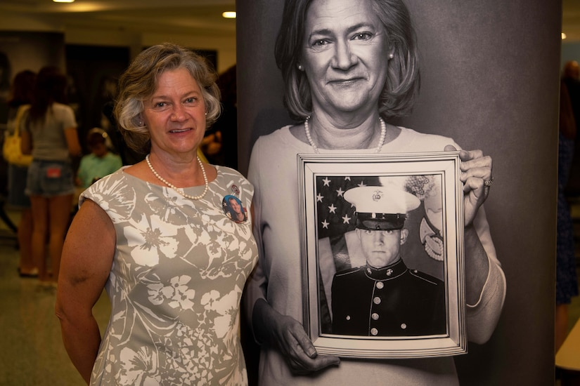 A woman poses next to a black and white photo of herself.