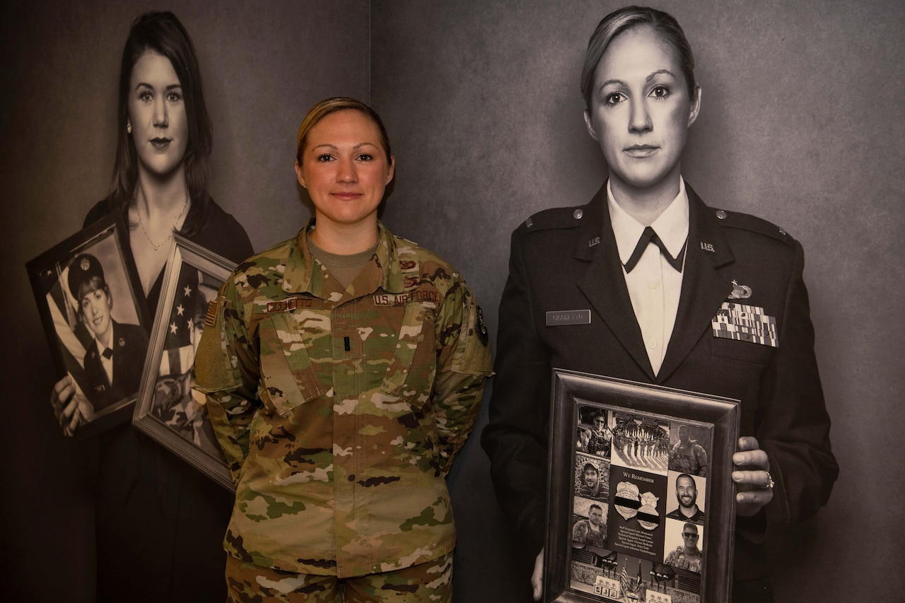 A woman poses next to a black-and-white photo of herself.