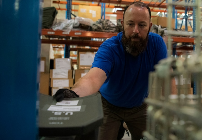 Paul Hight, 50th Logistics Readiness Flight mobility technician, stacks plates in the LRF warehouse at Schriever Air Force Base, Colorado, Aug. 14, 2019. While in-processing, Airmen are required to go to the warehouse to get fitted and issued different equipment, such as mission oriented protective posture gear. (U.S. Air Force photo by Airman 1st Class Jonathan Whitely)