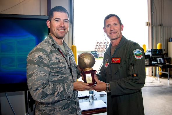 Col. John Gallemore, 57th Adversary Tactics Group commander, right, presents the U.S. Air Force Space Operator of the Year, company grade officer category, award to Capt. Nathaniel Lee, 527th Aggressor Squadron chief of future operations, at the 527th SAS barn, Schriever Air Force Base, Colorado, Aug. 15, 2019. In his role, Lee oversees and coordinates the unit's threat replication program, which mimics threats to the United States, allied space systems and their critical nodes. (U.S. Air Force photo by Kathryn Calvert)