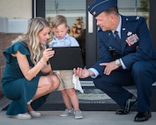 Alyssa Kidd and Beckham Kidd receive a replica of the plaque from Col. Michael Colvard, 2nd Maintenance Group commander, of what will go onto the newly named Kidd Weapons Load Training facility in honor of the late Tech. Sgt. Joshua L. Kidd Aug. 16, 2019, Barksdale Air Force Base, Louisiana.