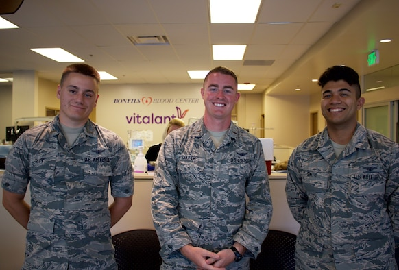 """From left, 2nd Lt. Jacob Diaz, 50th Operations Support Squadron student, 2nd Lt. Charles Cooper, 50th OSS student, and Airman 1st Class Kearey Smith, 50th OSS student, demonstrate """"service before self"""" during a blood drive in Colorado Springs, Colorado, Aug. 14, 2019. The 50th OSS organized the blood drive in response to mass shootings in the United States. (U.S. Air Force courtesy photo)"""