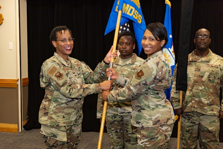 Lt. Col. Cynthia K. McGee, commander of the newly established 509th Healthcare Operations Squadron, ceremoniously returns the guide-on of the now inactivated 509th Medical Support Squadron to Col. Chrystal D. Henderson, commander of the 509th Medical Group, during a reorganization ceremony Aug. 14, 2019, at Whiteman Air force Base, Mo. Under the new Air Force Medical Reform model, dedicated provider care teams will be aligned to an Operational Medical Readiness Squadron primarily focused on proactively treating active-duty Airmen and improving their availability to support the warfighting mission. Care for non-active duty patients, primarily the families of service members and military retirees, will be handled by separate provider teams aligned to a Health Care Operations Squadron. (U.S. Air Force photo by Senior Airman Thomas Barley)