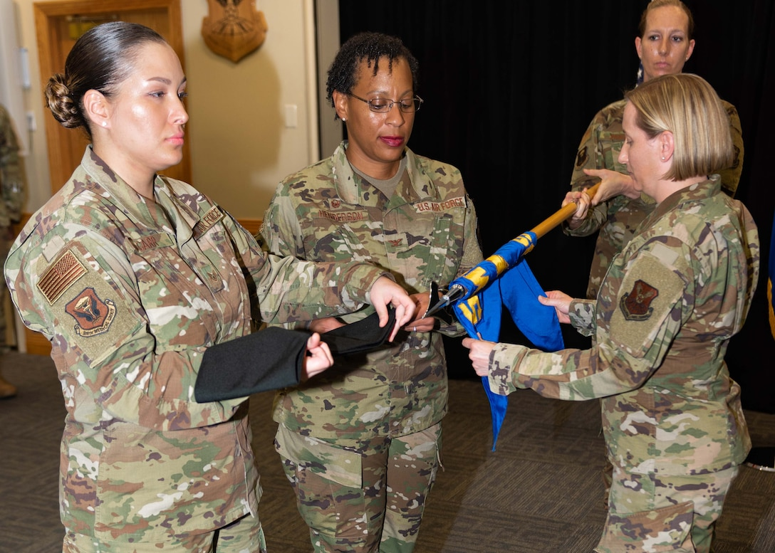 Col. Chrystal D. Henderson, commander of the 509th Medical Group, center, and Lt. Col. Stephanie A. Forsythe, commander of the 509th Medical Operations Squadron, unveil the new guide-on of the newly-established and activated 509th Operational Medical Readiness Squadron during a reorganization ceremony Aug. 14, 2019, at Whiteman Air Force Base, Mo. Under the new Air Force Medical Reform model, dedicated provider care teams will be aligned to an Operational Medical Readiness Squadron primarily focused on proactively treating active-duty Airmen and improving their availability to support the warfighting mission. Care for non-active duty patients, primarily the families of service members and military retirees, will be handled by separate provider teams aligned to a Health Care Operations Squadron. Forsythe was the commander of the now inactivated Medical Operations Squadron and assumed command of the new unit from Henderson. (U.S. Air Force photo by Senior Airman Thomas Barley)